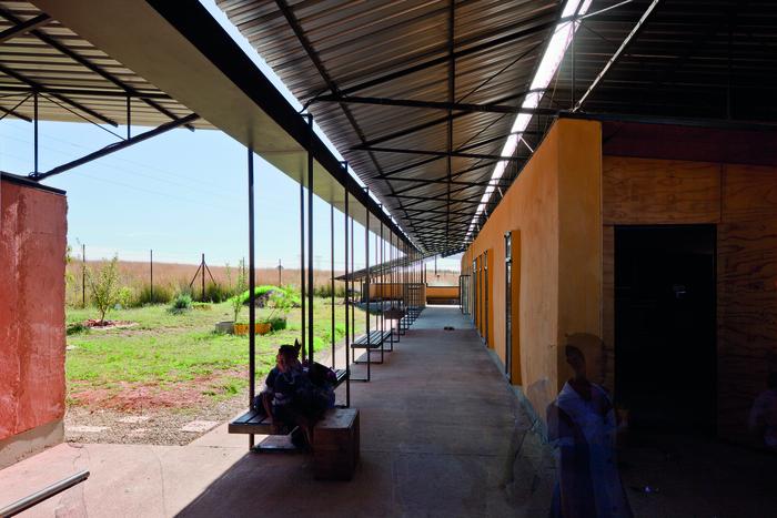 """Foto Das Projekt Iphiko Classrooms zeigt eine gute Kombination von """"Hand made""""- Lehmbauweise, die sich klimatisch hier besonders gut eignet, und einer einfachen, zarten Stahlkonstruktion mit Verblechung als Dach. Wenn vorgefertigte oder industriell hergestellte Konstruktionen sinnvoll und günstig sind, bieten sie eine gute Ergänzung zu den Selbstbauelementen. © BASEhabitat - Kunstuniversität Linz"""